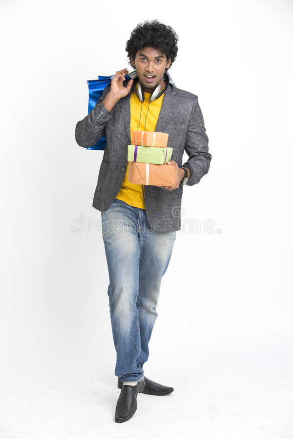 Overloaded Indian young man surprise with shopping bags and gift boxes royalty free stock images