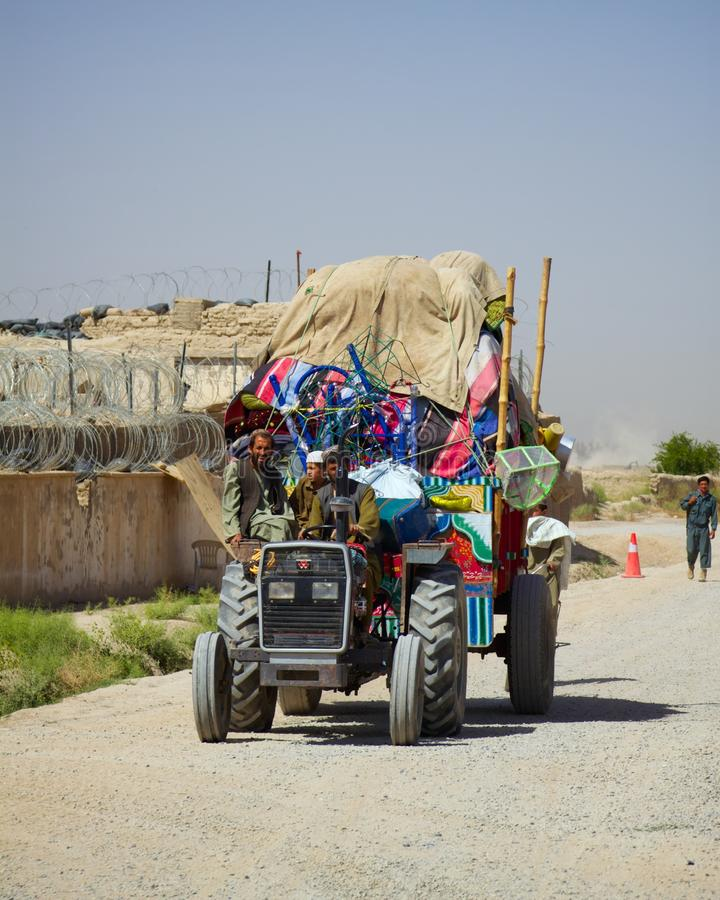 An overloaded tractor in Kandahar Afghanistan. A group of Afghan farmers drive a heavily overloaded tractor past an Afghan Police station in Kandahar Province stock photos