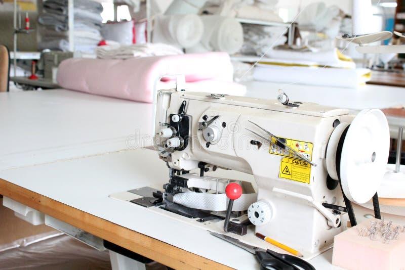 Overlock profissional da máquina de costura na oficina Equipamento para a roupa da afiação, da orladura ou da costura em uma loja fotos de stock