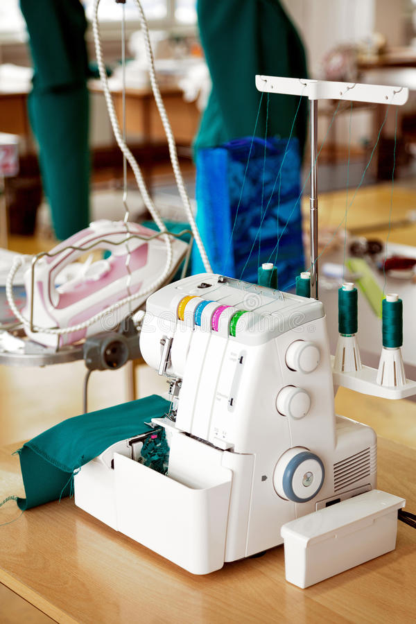 Overlock sewing machine in tailor office. Fashion designer equipment serger in a sewing workshop. Green mannequins on the background stock images