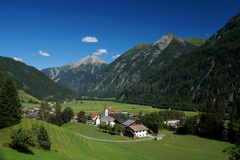 Overlook of the township of Holzgau amid the foothills of the Austrian Alps. Vista of a rural alpine township in the Lech Valley which is bounded geographically