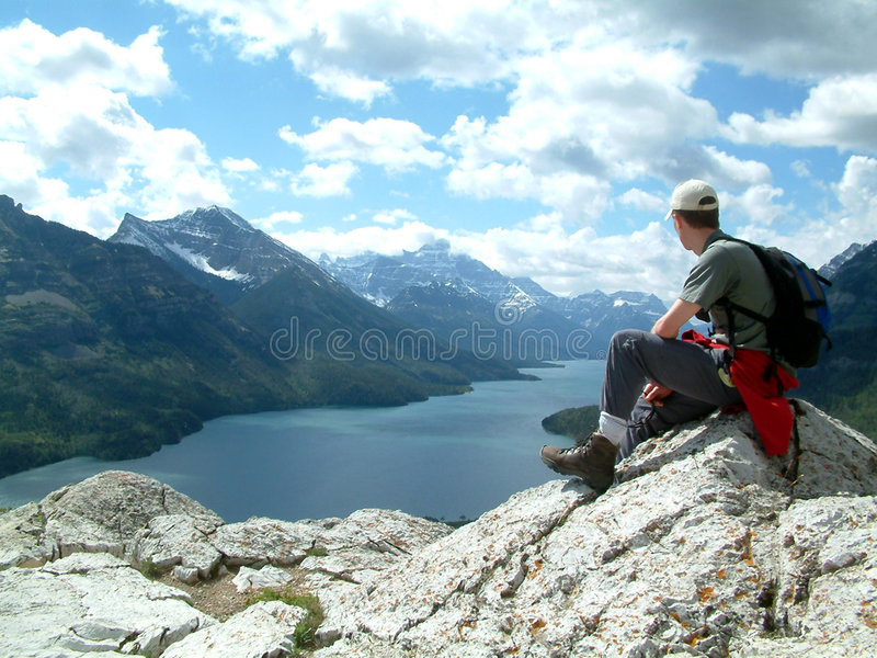 Overlooking. Man sitting on top of mountain