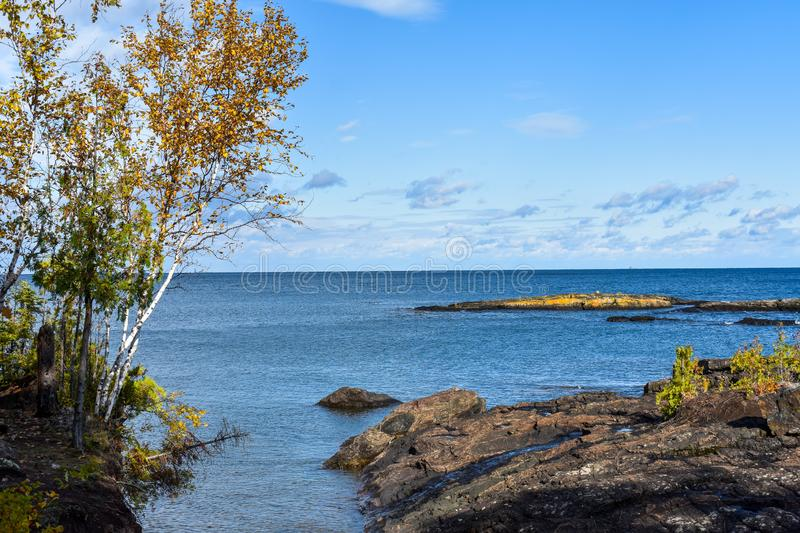 Overlooking Lake Superior from Rescue Isle, Marquette Michigan from volcanic rocks. Lake Superior coastline Presque Isle, Marquette, Michigan. Birch trees royalty free stock photo