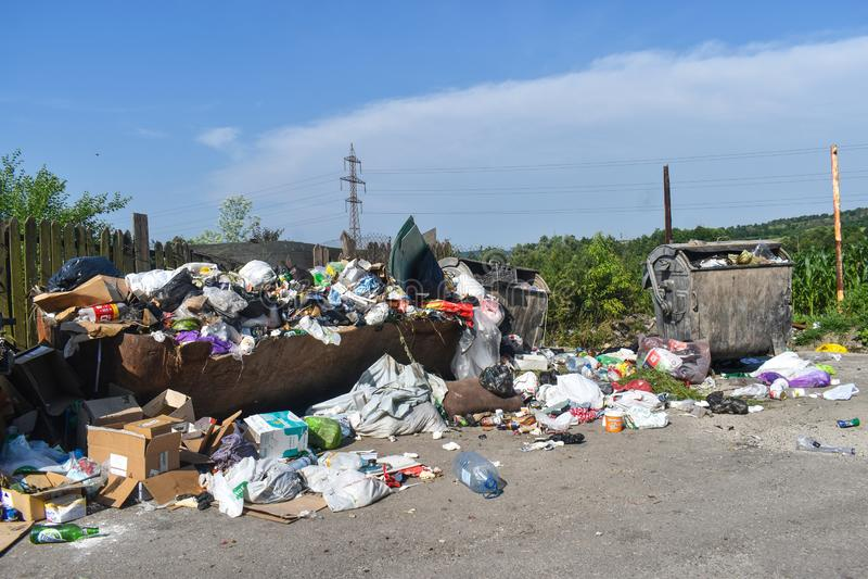 Overlopende vuilnisbak in de stad De overstroming van vuilnisbakken met vuilnis en geworpen op de vloer De bakken zijn niet leegg stock afbeelding