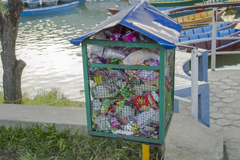 Overlopende vuilnisbak dichtbij een bank in een park door het meer met boten stock afbeeldingen