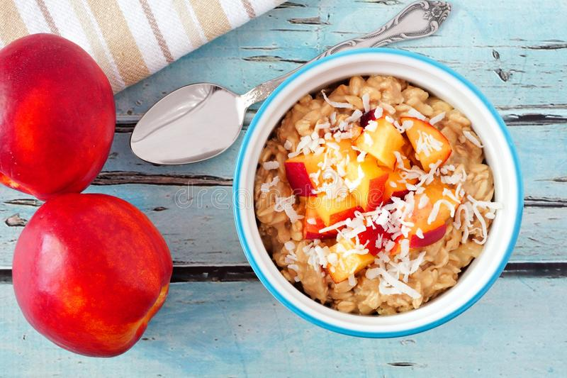 Overnight breakfast oats with peach and coconut, overhead scene royalty free stock image