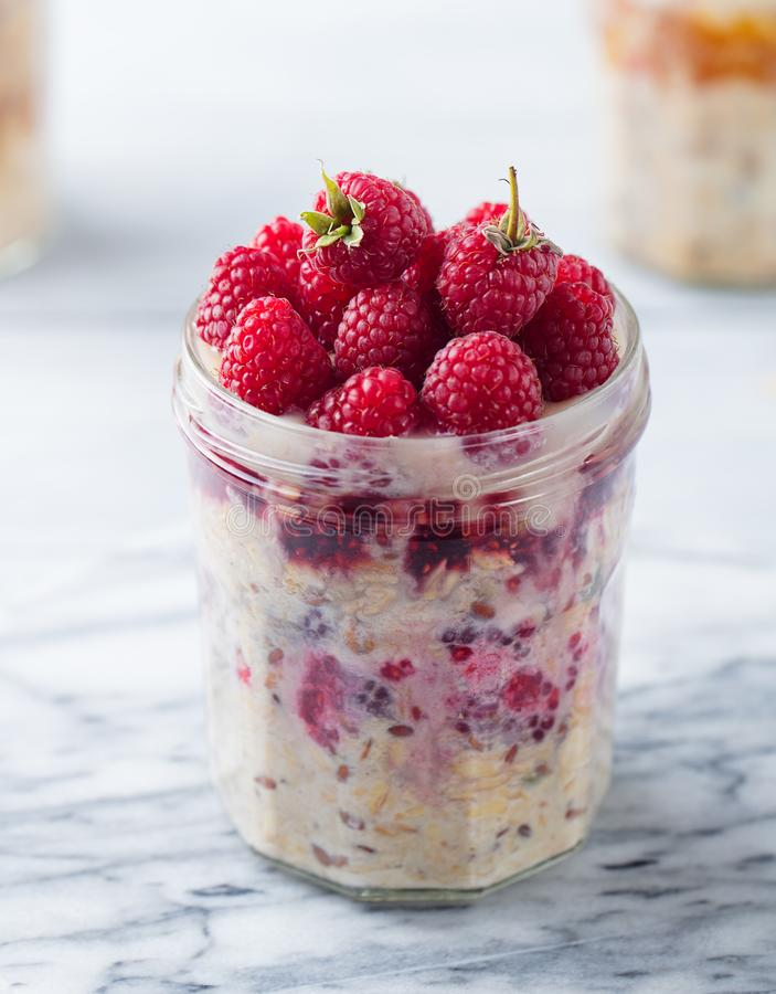 Overnight oats, bircher muesli with raspberry in a glass jar on marble background. Close up. royalty free stock photography