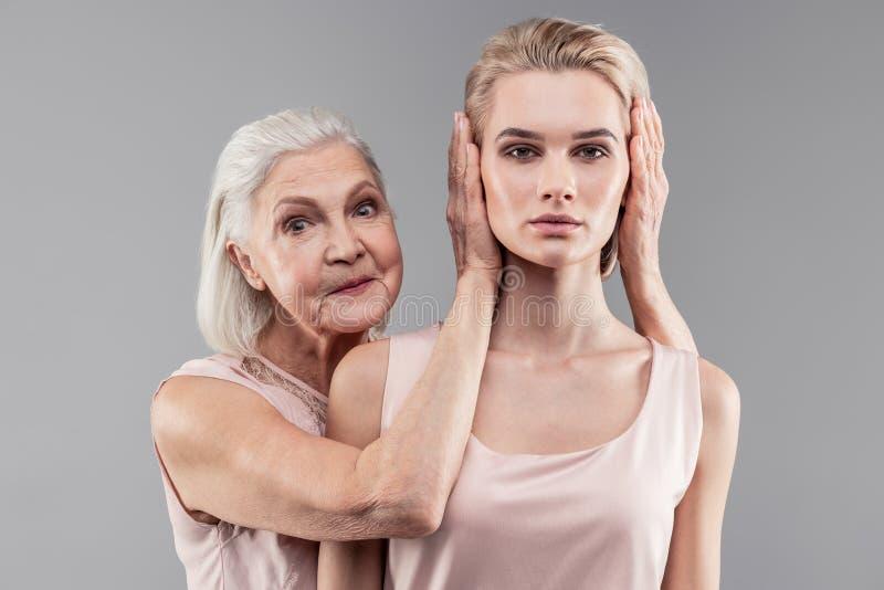 Overprotective senior matki końcowi ucho dorosła córka obraz royalty free
