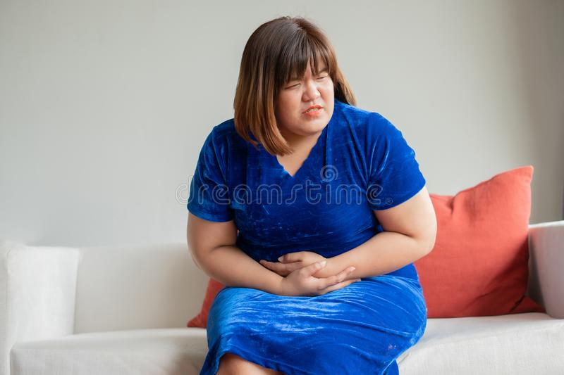 Oversize asian woman sitting on sofa in living room. Her upset and unhappy and holding hands on stomach suffering from abdominal p royalty free stock photo