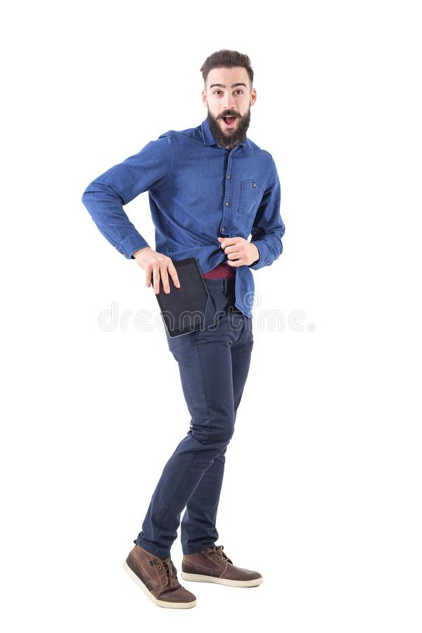 Oversize cell phone concept. Funny man trying to put large smart phone or tablet in jeans pocket. Full body isolated on white background royalty free stock photos