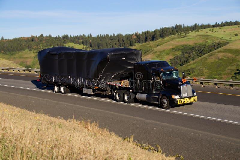 Oversize Load / Black Kenworth Semi-Truck stock photography