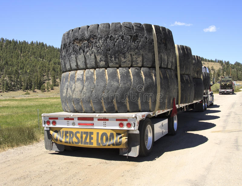 Oversize load truck. A large trailer truck carrying an oversize load of used tires stock image