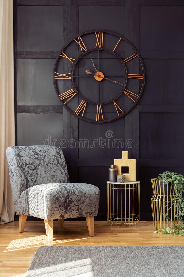 Oversized wall clock, armchair and golden table with a vase in a living room interior. Real photo. Concept royalty free stock photography
