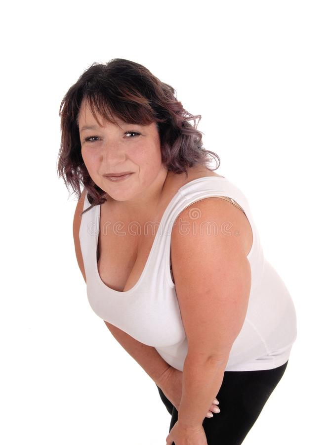 Oversized woman bending forwards. A pretty middle age woman in a white t-shirt standing isolated for white background bending forwards royalty free stock photos