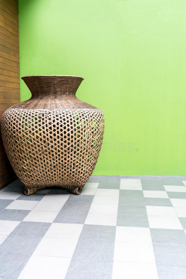 Oversized wooden weave vase standing in corner of wooden and yel stock photos