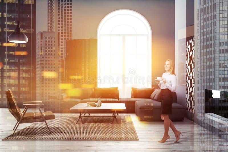 Overspannen grijze woonkamer, leunstoel en bank, vrouw royalty-vrije stock afbeeldingen