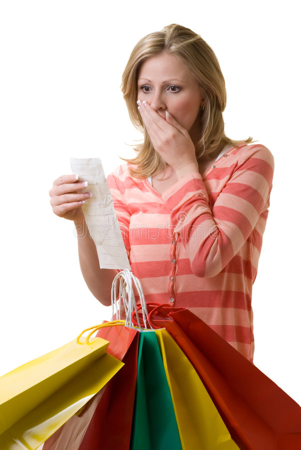 Overspending. Attractive blond woman standing in front of a bunch of colorful shopping bags checking over the receit with a worried expression