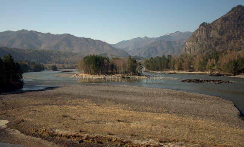 Overstroomde banken van de lente van de rivier met een eiland in het midden van het kanaal dat door bergen wordt omringd stock foto