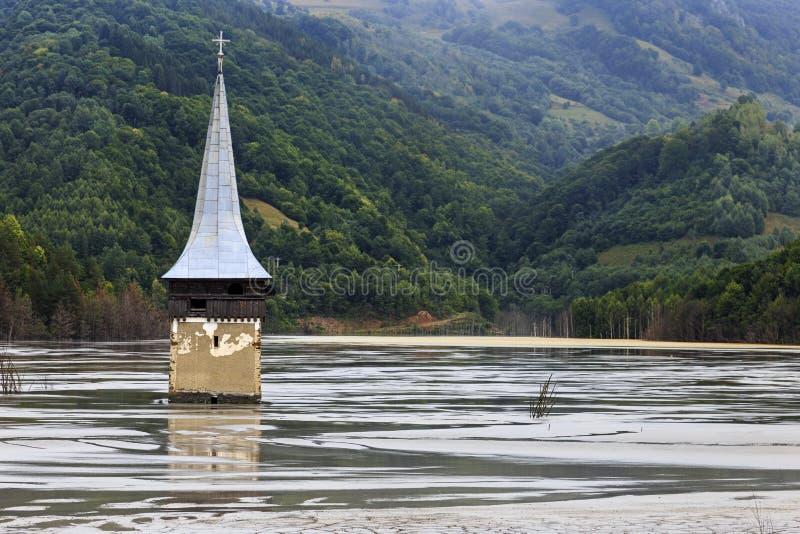 Overstroomde kerk in verontreinigd meer stock fotografie