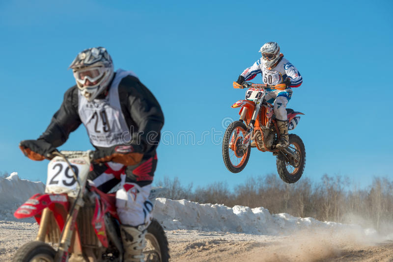 Overtaking by air. BORODINO, RUSSIA - FEBRUARY 5: Unidentified riders drive during at the all-Russian motocross named VP Chkalov, the organizer of the Auto stock photo