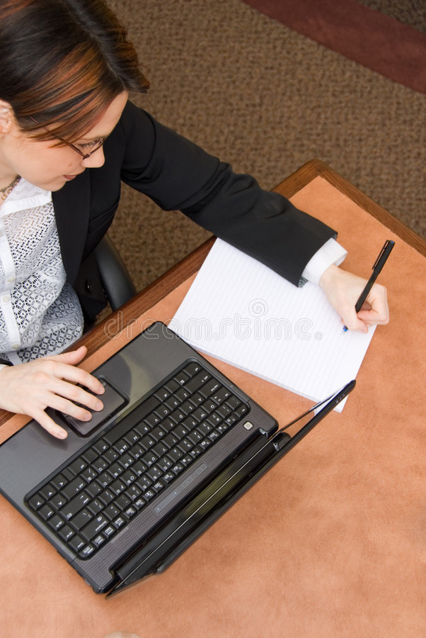 Overtime. Woman in a boardroom taking some notes royalty free stock photo