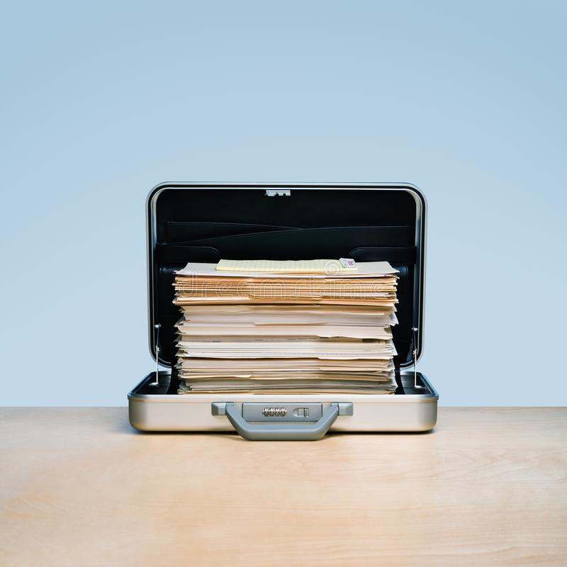 Overtime, pile of files and folders in aluminum briefcase. royalty free stock photo
