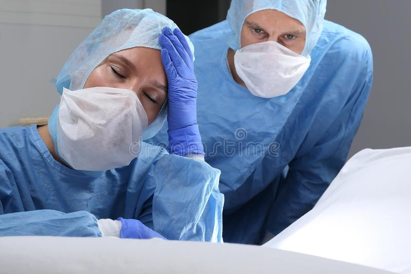 Overtired or angry doctor doing a surgery stock images