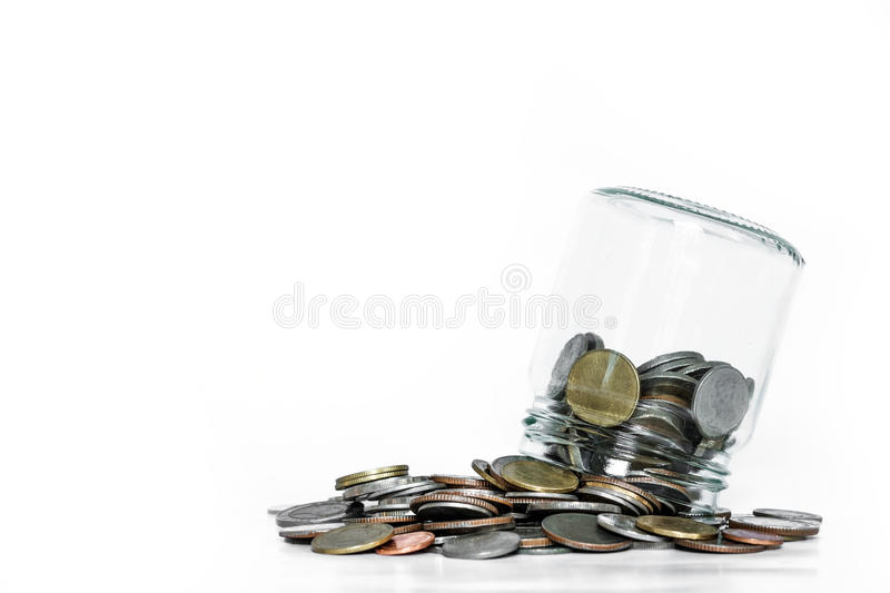 Overturn glass jar with coins spilled out, on white background stock photography