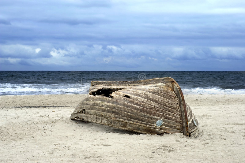 Overturned boat on beach stock images