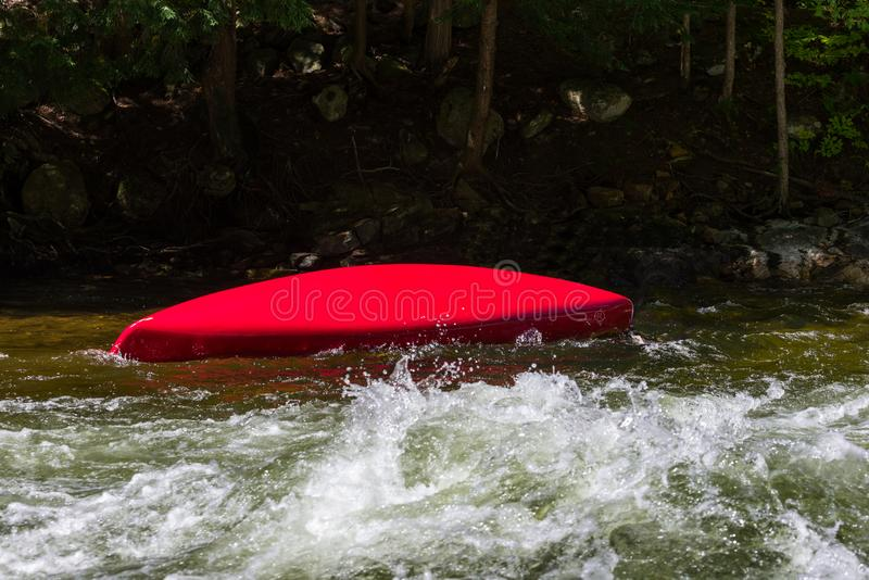 Overturned canoe in rapids royalty free stock images