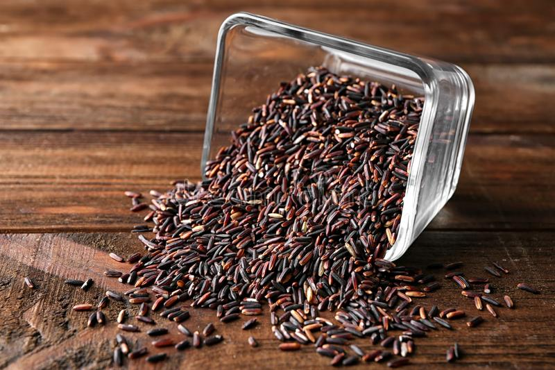 Overturned glass bowl with wild rice on background royalty free stock photography