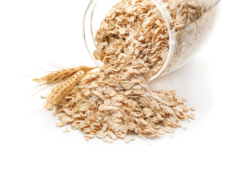 Overturned glass jar with raw oatmeal on white background, closeup stock photo