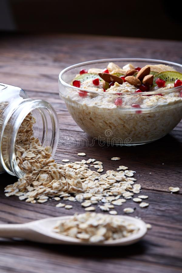 Overturned glass jar and spoon with raw oatmeal on vintage wooden background, close-up, selective focus. royalty free stock photography