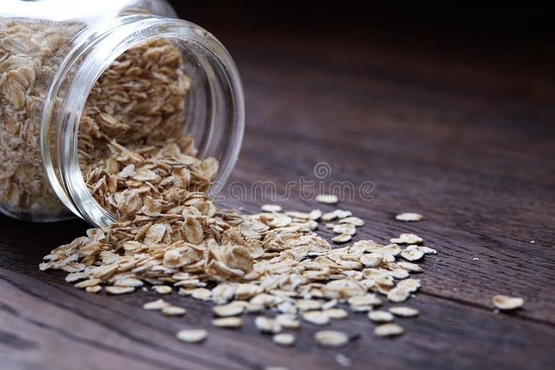 Overturned glass jar and spoon with raw oatmeal on vintage wooden background, close-up, selective focus. stock photo