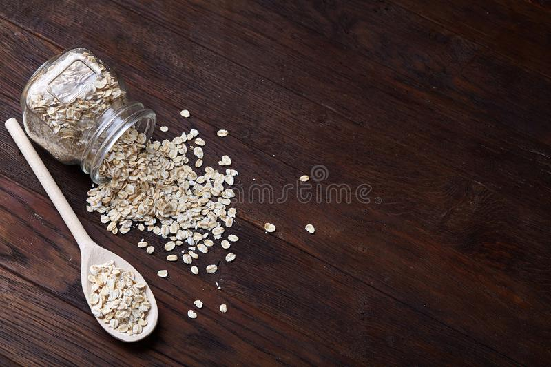 Overturned glass jar and spoon with raw oatmeal on vintage wooden background, close-up, selective focus. stock photography