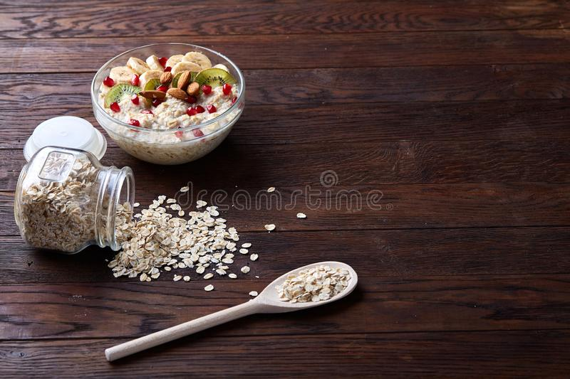 Overturned glass jar and spoon with raw oatmeal on vintage wooden background, close-up, selective focus. stock photos