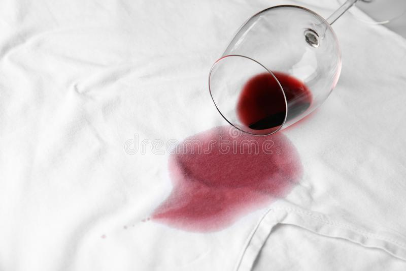 Overturned glass and spilled exquisite red wine on t-shirt. Space for text. Overturned glass and spilled exquisite red wine on white t-shirt. Space for text royalty free stock photo