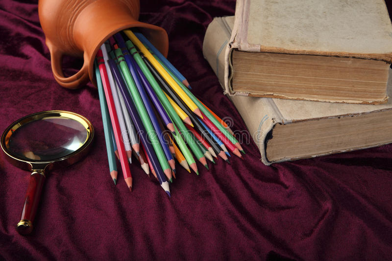 Overturned jug with colored pencils, magnifying glass and old books on the desk. Stylized view of retro objects. stock photo