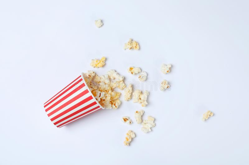 Overturned paper cup with tasty popcorn on white background stock image