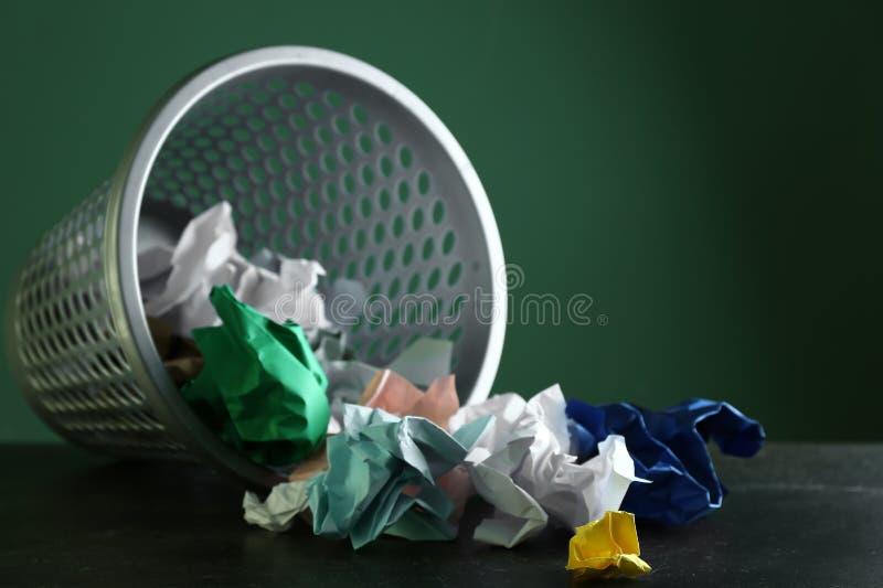 Overturned ricicla il recipiente con le carte sgualcite sulla tavola contro il fondo di colore fotografia stock libera da diritti