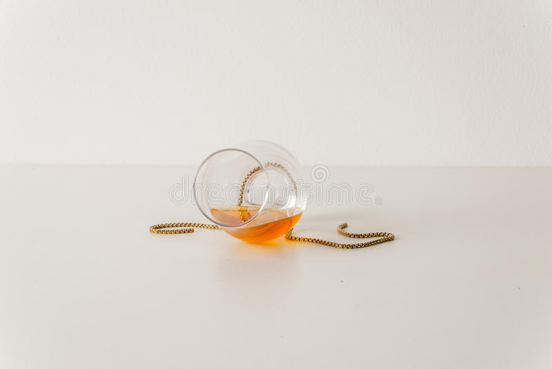 Overturned single malt whiskey glass, on white, with gold chain stock photography