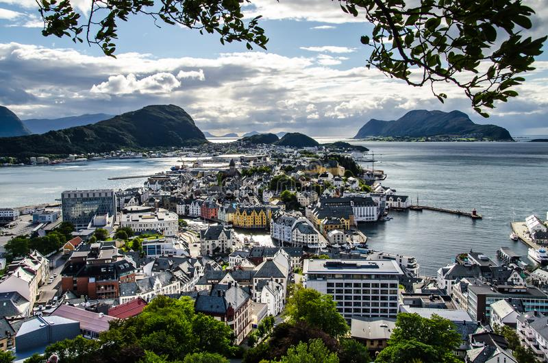 Overview of Alesund town from the Aksla viewpoint during the late evening before sunset with tree leaves framing.  stock photos