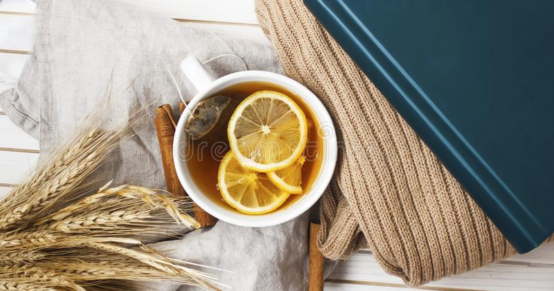 Top view of warm tea mug. Overview background  of warm cup of tea with sliced lemon, cinnamon, wheat , book and pullover on white surface stock photography