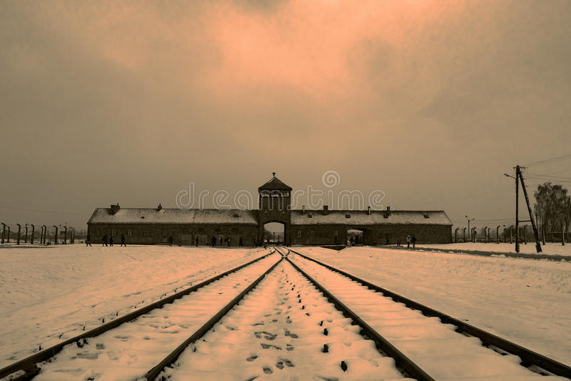 Overview of Birkenau concentration camp and rails in the fog and. Overview from the inside of the main building of the Birkenau camp in the fog and snow at stock photos