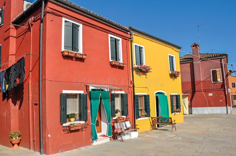 Overview of colorful buildings and clothes hanging in a blue sunny day, in Burano. stock images