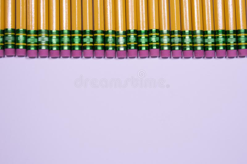 Line of pencil erasers on white background with copy space stock image