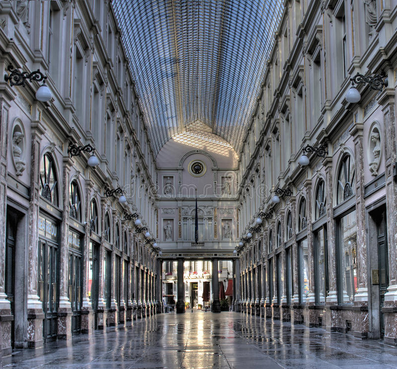 Overview shot of the galeries St Hubert in Brussel. The just-cleaned floor of the majestic Galleries st Hubert is reflecting the first rays of sun at sunrise royalty free stock images