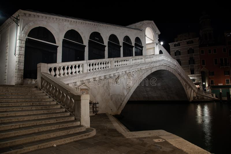 Night photo Rialto Bridge in Venice, Italy. Overview of the white marble bridge illuminated by reflections on the water of the Grand Canal stock image