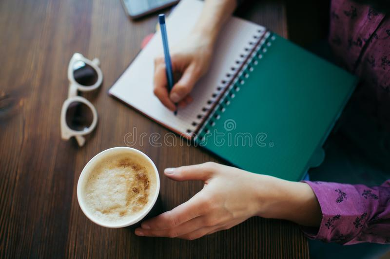 Overview of woman`s hands holding both coffee and pen. stock images