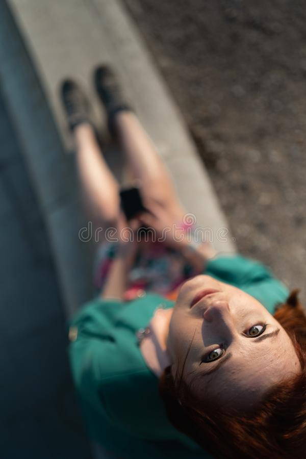 Overview of a young woman uses phone in a palace park sitting on a fountain - View from above royalty free stock photos